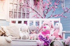 Ours de nounours, lapin et caniche de peluche se reposant sur le banc en bois blanc Image libre de droits