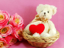 Ours de nounours mignon avec le coeur rouge dans le panier avec le fond rose Images stock