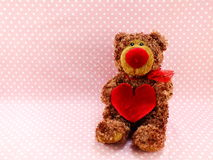 Ours de nounours mignon avec le coeur rouge sur le fond rose Image stock