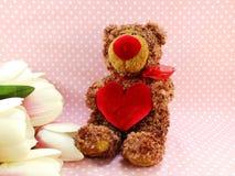 Ours de nounours mignon avec le coeur rouge sur le fond rose Photo libre de droits