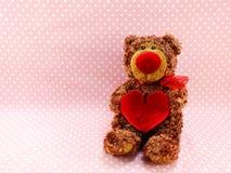 Ours de nounours mignon avec le coeur rouge sur le fond rose Image libre de droits