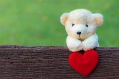 Ours de nounours mignon avec le coeur rouge sur le vieux bois, l'espace de copie Photographie stock libre de droits