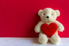 Ours de nounours mignon avec le coeur rouge sur le vieux bois, l'espace de copie, fond rouge Photo stock