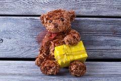 Ours de nounours mignon avec un cadeau Boîte-cadeau jaune des ours dans le sien a Image stock