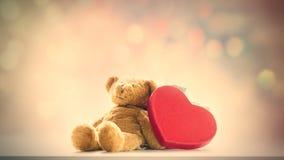 Ours de nounours mignon et beau jouet en forme de coeur sur le ligh féerique Photos stock