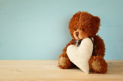 Ours de nounours mignon reposant et tenant un coeur Photo stock