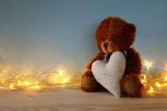 Ours de nounours mignon reposant et tenant un coeur Photo libre de droits