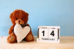 Ours de nounours mignon reposant et tenant un coeur Photos libres de droits