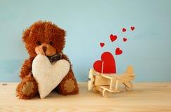 Ours de nounours mignon reposant et tenant un coeur Photographie stock