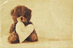 Ours de nounours mignon reposant et tenant un coeur Image libre de droits