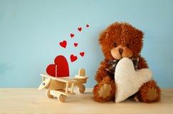 Ours de nounours mignon reposant et tenant un coeur Images stock