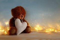 Ours de nounours mignon reposant et tenant un coeur Images libres de droits