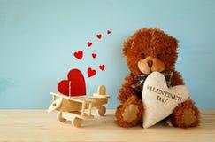 Ours de nounours mignon reposant et tenant un coeur Photos stock