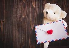 Ours de nounours mignon saisissant la lettre d'amour dans des ses bras sur le fond en bois, Photos stock