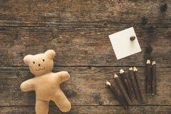 Ours de nounours, note collante et crayons Photographie stock