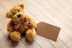 Ours de nounours pelucheux mignon avec le label sur l'en bois brun merveilleux Images stock