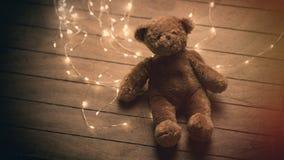 Ours de nounours pelucheux mignon et guirlande lumineuse sur le brun merveilleux Photos stock