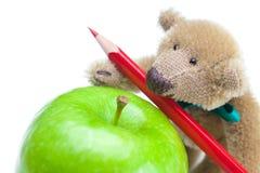 Ours de nounours, pomme et crayons colorés Photographie stock libre de droits