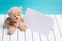 Ours de nounours se reposant sur le plancher en bois blanc à l'arrière-plan bleu-vert avec la note vide Images stock