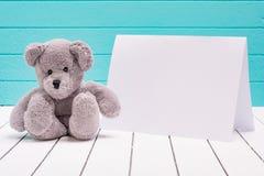 Ours de nounours se reposant sur le plancher en bois blanc à l'arrière-plan bleu-vert avec la note vide Photographie stock libre de droits