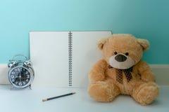 Ours de nounours tenant l'horloge brillante avec le carnet de page vide et Photographie stock