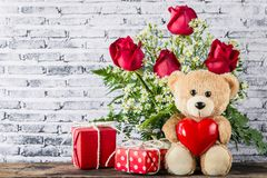Ours de nounours tenant un ballon en forme de coeur avec le boîte-cadeau rouge Photos libres de droits
