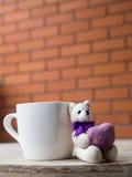 Ours de nounours tenant un coeur pourpre Ours de nounours à côté du café blanc Photographie stock libre de droits