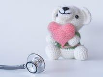 Ours de stéthoscope et de nounours tenant un coeur sur le fond blanc Photos libres de droits