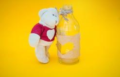 Ours et bouteille sur le fond jaune Image stock