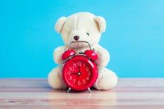 Ours et montre rouge placés sur une table en bois bleue Photos libres de droits