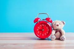 Ours et rétro rouge de montre placés sur une table en bois bleue Images libres de droits
