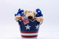 Ours patriotique dans le seau Photographie stock