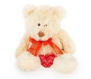 Ours velu avec un arc rouge et un coeur rouge Photographie stock