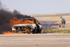 Out of control. Man trying to stop a grass fire royalty free stock photos