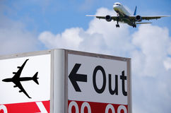 Out directional sign at airport with plane in back Stock Images