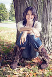 Out Doorsy Young Woman Leaning Against Tree in Fall royalty free stock photos