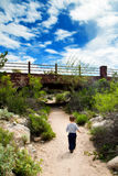 Out Exploring. Toddler boy explores a desert path. He walks boldly towards a bridge under a bright blue and cloudy sky. The image has a dreamy, nostalgic look Stock Photos