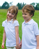 Out in the field. A set of boy/girl twins in a field of green grass Stock Photo