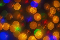 Out of focus and blurred colored star shape lights on black background.  Royalty Free Stock Images