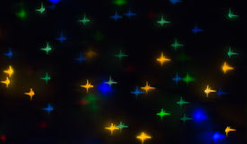 Out of focus and blurred colored star shape lights on black background.  Royalty Free Stock Image