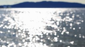 Out-of-focus bokeh dancing lights body of water on a bright sunny day 1080p HD stock footage