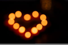 Out of focus candles forming heart. Out of focus candles with light forming heart royalty free stock images