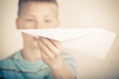 Out of focus child holding paper airplane Stock Photography