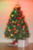 Out of focus Christmas tree with one gift Stock Image