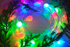 Out of focus colored lights and garlands of Christmas tree branc Royalty Free Stock Images