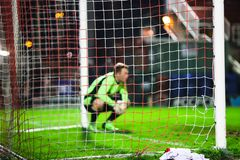Out of focus goalkeeper crouching down near the goal post stock photography