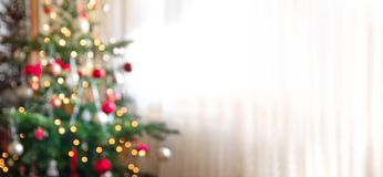 Out of focus holiday background with christmas tree. Christmas tree against bright window curtain, blurred christmas background stock photo