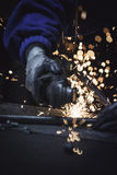 Out of focus image of industrial worker cutting metal pipe with sharp sparks background. Vertical Stock Image