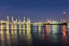 Out of focus, Oil refinery at twilight with river reflection Stock Images