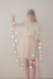 Out of focus portrait of girl unwrapping Christmas lights. Out of focus portrait of young girl unwrapping colorful Christmas lights Stock Images